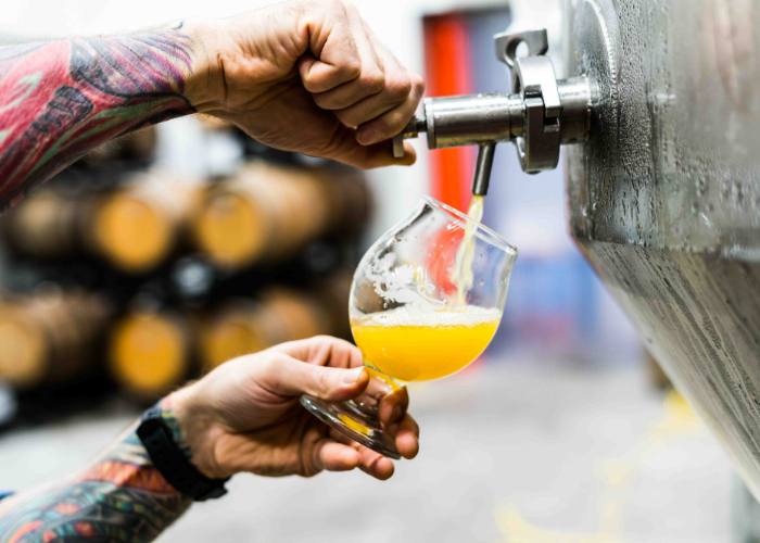 man with tattoos pouring beer from a keg into a glass