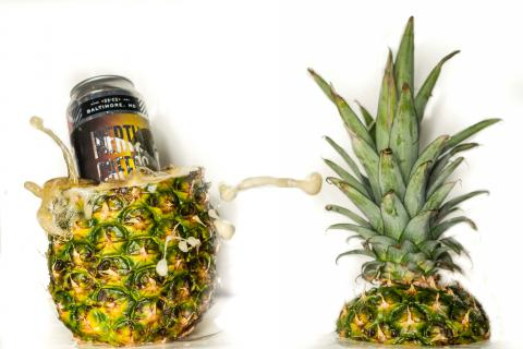 beer can in a pineapple next to the top of the pineapple